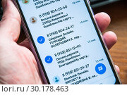 Купить «Смартфон с мошенническими сообщениями в руке», эксклюзивное фото № 30178463, снято 23 февраля 2019 г. (c) Алёшина Оксана / Фотобанк Лори