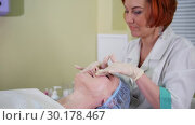 Купить «A massage treatment in cosmetology clinic. Ginger woman doctor distributes cream on client face», видеоролик № 30178467, снято 23 марта 2019 г. (c) Константин Шишкин / Фотобанк Лори