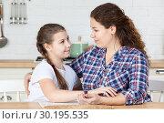 Мама и дочь подросток смотрят друг на друга с любовью за столом в кухне. Стоковое фото, фотограф Кекяляйнен Андрей / Фотобанк Лори
