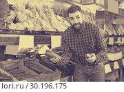 Купить «Cheerful male seller offering cucumbers in shop», фото № 30196175, снято 15 ноября 2016 г. (c) Яков Филимонов / Фотобанк Лори
