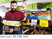 Купить «man seller showing pears», фото № 30196183, снято 15 ноября 2016 г. (c) Яков Филимонов / Фотобанк Лори