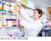 Купить «Adult is browsing rows of body care products», фото № 30196243, снято 31 января 2017 г. (c) Яков Филимонов / Фотобанк Лори