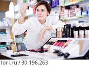 Купить «Glad female customer looking for make-up items», фото № 30196263, снято 31 января 2017 г. (c) Яков Филимонов / Фотобанк Лори