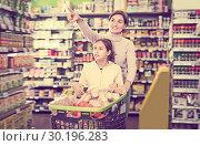 Купить «Glad woman and daughter with shopping cart», фото № 30196283, снято 5 января 2017 г. (c) Яков Филимонов / Фотобанк Лори