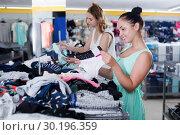 Купить «Young happy females selecting new basics pants», фото № 30196359, снято 19 июня 2017 г. (c) Яков Филимонов / Фотобанк Лори
