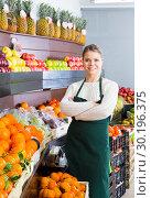 Купить «Attractive female in apron selling fresh oranges», фото № 30196375, снято 18 июля 2019 г. (c) Яков Филимонов / Фотобанк Лори