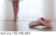 Купить «Young woman ballerina training in bright studio. Pointe shoes on the foreground», видеоролик № 30196483, снято 27 мая 2020 г. (c) Константин Шишкин / Фотобанк Лори