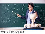Купить «Young male math teacher and student skeleton», фото № 30196883, снято 19 октября 2018 г. (c) Elnur / Фотобанк Лори