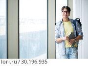Купить «Young handsome student standing at the window», фото № 30196935, снято 2 августа 2018 г. (c) Elnur / Фотобанк Лори