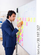 Купить «Young handsome employee in front of whiteboard with to-do list», фото № 30197327, снято 16 октября 2018 г. (c) Elnur / Фотобанк Лори