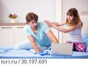 Купить «Young couple with laptop in the bedroom», фото № 30197691, снято 19 сентября 2018 г. (c) Elnur / Фотобанк Лори