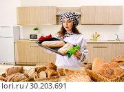 Купить «Young female baker working in kitchen», фото № 30203691, снято 2 ноября 2018 г. (c) Elnur / Фотобанк Лори