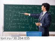 Купить «Young male math teacher in classroom», фото № 30204035, снято 11 октября 2018 г. (c) Elnur / Фотобанк Лори