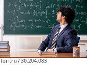 Купить «Young male math teacher in classroom», фото № 30204083, снято 11 октября 2018 г. (c) Elnur / Фотобанк Лори