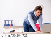 Купить «Young handsome employee working in the office», фото № 30204723, снято 5 октября 2018 г. (c) Elnur / Фотобанк Лори