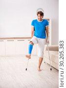 Купить «Leg injured young man with crutches at home», фото № 30205383, снято 19 сентября 2018 г. (c) Elnur / Фотобанк Лори
