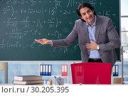 Купить «Young handsome math teacher in classroom», фото № 30205395, снято 20 ноября 2018 г. (c) Elnur / Фотобанк Лори