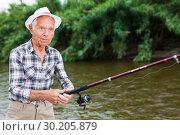 Купить «Mature man angling at riverside», фото № 30205879, снято 10 июня 2018 г. (c) Яков Филимонов / Фотобанк Лори