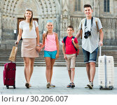 Traveling family of four strolling with luggage along European city street. Стоковое фото, фотограф Яков Филимонов / Фотобанк Лори
