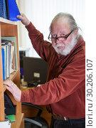 Купить «Мужчина в возрасте, в очках и с седой бородой стоит у шкафа с документами», фото № 30206107, снято 22 февраля 2019 г. (c) Кекяляйнен Андрей / Фотобанк Лори