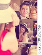 Купить «man holding mirror and showing customer his reflection in hats shop», фото № 30206159, снято 2 мая 2017 г. (c) Яков Филимонов / Фотобанк Лори
