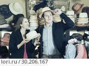 Купить «young wife and husband choosing dress hats in the store», фото № 30206167, снято 2 мая 2017 г. (c) Яков Филимонов / Фотобанк Лори