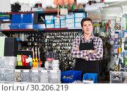 Купить «Man standing near the counter and selling details for plumbing in hardware shop», фото № 30206219, снято 4 мая 2017 г. (c) Яков Филимонов / Фотобанк Лори