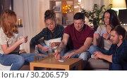 Купить «friends playing cards game at home in evening», видеоролик № 30206579, снято 12 января 2019 г. (c) Syda Productions / Фотобанк Лори