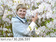 Купить «Зрелая женщина на фоне цветущего рододендрона Шлиппенбаха», фото № 30206591, снято 3 мая 2016 г. (c) Ирина Борсученко / Фотобанк Лори