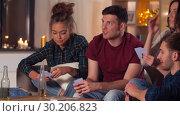 Купить «friends playing cards game at home in evening», видеоролик № 30206823, снято 12 января 2019 г. (c) Syda Productions / Фотобанк Лори