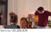 Купить «happy friends playing charades at home in evening», видеоролик № 30206839, снято 12 января 2019 г. (c) Syda Productions / Фотобанк Лори