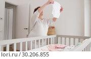 Купить «happy pregnant woman setting baby clothes at home», видеоролик № 30206855, снято 18 февраля 2019 г. (c) Syda Productions / Фотобанк Лори