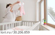 Купить «happy pregnant woman setting baby clothes at home», видеоролик № 30206859, снято 18 февраля 2019 г. (c) Syda Productions / Фотобанк Лори