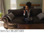 Купить «Female real estate agent talking on mobile phone while using digital tablet in living room», фото № 30207643, снято 7 ноября 2018 г. (c) Wavebreak Media / Фотобанк Лори