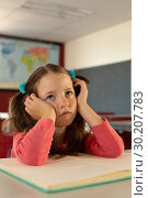 Купить «Sad girl leaning on desk in a classroom at school», фото № 30207783, снято 10 ноября 2018 г. (c) Wavebreak Media / Фотобанк Лори