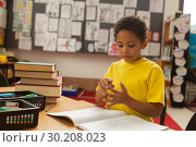 Купить «Schoolboy counting with his finger at desk in a classroom», фото № 30208023, снято 17 ноября 2018 г. (c) Wavebreak Media / Фотобанк Лори