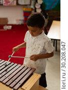 Купить «Schoolboy playing xylophone in a classroom», фото № 30208047, снято 17 ноября 2018 г. (c) Wavebreak Media / Фотобанк Лори