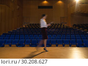 Купить «Businesswoman practicing and learning script while walking in the auditorium», фото № 30208627, снято 15 ноября 2018 г. (c) Wavebreak Media / Фотобанк Лори
