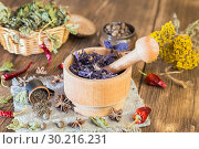 Купить «Fragrant dried healing herbs for therapy and spicy spices. On the table in a mortar are purple basil, tansy, pepper, chili and cardamom, in a rustic style», фото № 30216231, снято 16 февраля 2019 г. (c) Светлана Евграфова / Фотобанк Лори