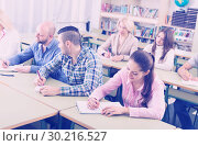 Adult students writing in classroom. Стоковое фото, фотограф Яков Филимонов / Фотобанк Лори