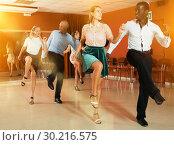 Купить «Young positive people dancing twist together at modern dance studio», фото № 30216575, снято 4 октября 2018 г. (c) Яков Филимонов / Фотобанк Лори