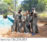 Купить «Cheerful group of paintball players in full gear making selfie with smartphone outdoors», фото № 30216851, снято 11 августа 2018 г. (c) Яков Филимонов / Фотобанк Лори