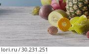 Купить «Panoramic slow motion of tropic fruits - pineapple, coconut, pitahaya on a wooden table on a blue. Motion, 4K UHD video, 3840, 2160p. Close-up», видеоролик № 30231251, снято 4 июля 2018 г. (c) Ярослав Данильченко / Фотобанк Лори