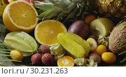 Купить «Assorted tropical fruits - halves of orange, pineapple, carambola, coconut and lichi with watering. Motion, 4K UHD video, 3840, 2160p.», видеоролик № 30231263, снято 4 июля 2018 г. (c) Ярослав Данильченко / Фотобанк Лори