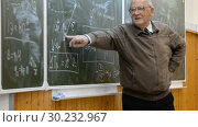 Professor teacher (real, not an artist) gives a lecture on physics, mathematics at the blackboard at the university. Close-up. Стоковое видео, видеограф Mikhail Erguine / Фотобанк Лори