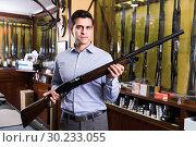 Купить «Handsome adult male in hunting shop with rifle in hands», фото № 30233055, снято 11 декабря 2017 г. (c) Яков Филимонов / Фотобанк Лори