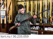 Confident hunter male wearing windbreaker in hunting shop with r. Стоковое фото, фотограф Яков Филимонов / Фотобанк Лори