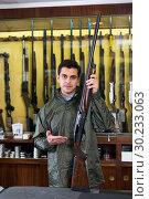 Купить «Portrait of cheerful confident man showing rifle», фото № 30233063, снято 11 декабря 2017 г. (c) Яков Филимонов / Фотобанк Лори
