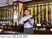 Купить «Salesman showing rifle», фото № 30233087, снято 11 декабря 2017 г. (c) Яков Филимонов / Фотобанк Лори