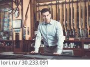 Купить «Handsome adult male owner of hunting shop offering rifle», фото № 30233091, снято 11 декабря 2017 г. (c) Яков Филимонов / Фотобанк Лори